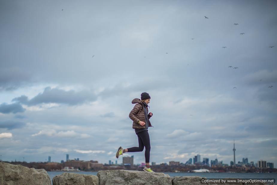 صورة فتاه تجرى على الصخور وسط البحر