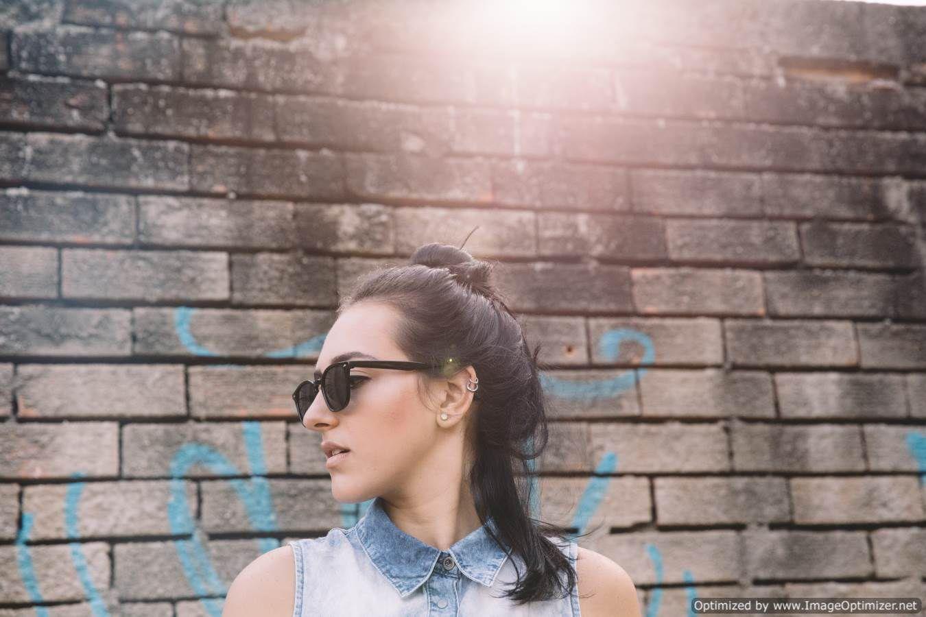 صورة بنت جميلة تلبس نظارة شمس وتنظر بجانبها