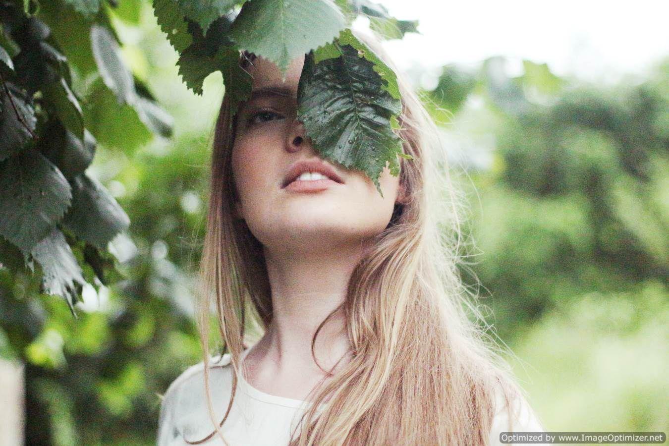 صورة فتاه جميلة تغطى عينها اليسرى بورقه شجر خضراء